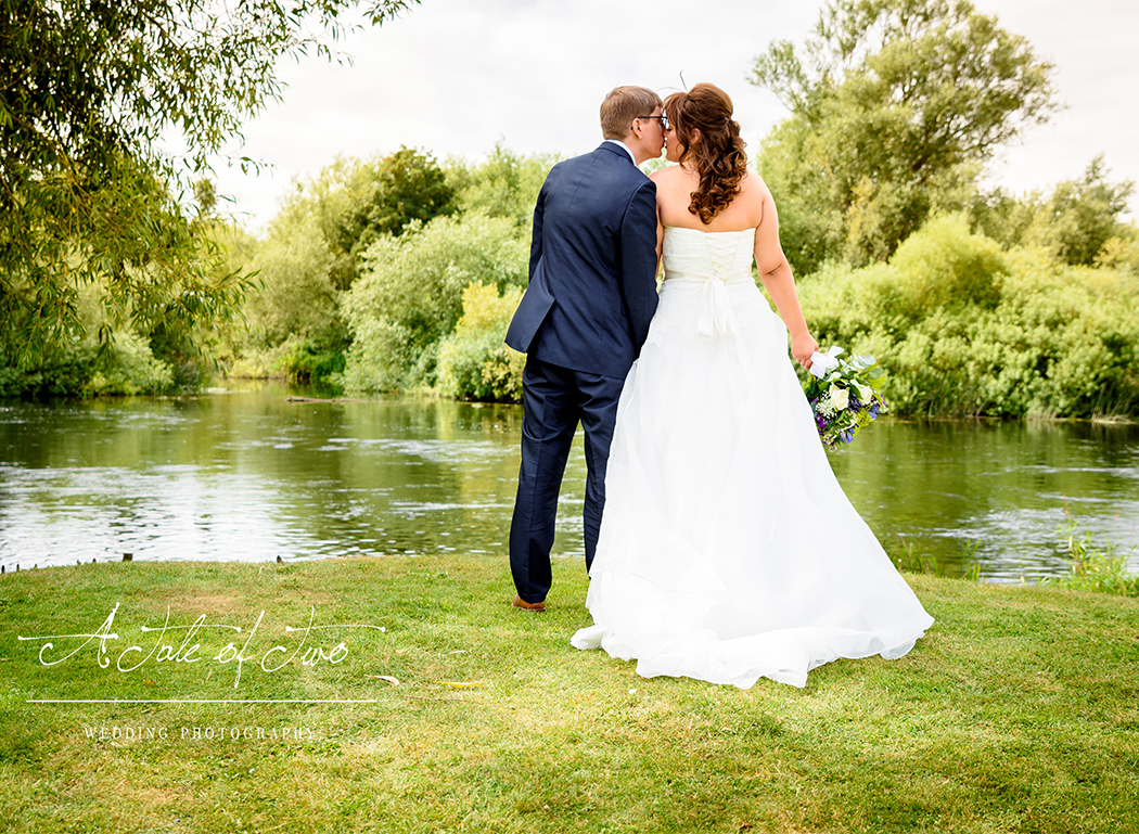 Hannah and Daniel kiss by the river on their wedding day, taken at The Priest House Hotel, Castle Donnington...for booking info please visit www.ataleoftwo.co.uk