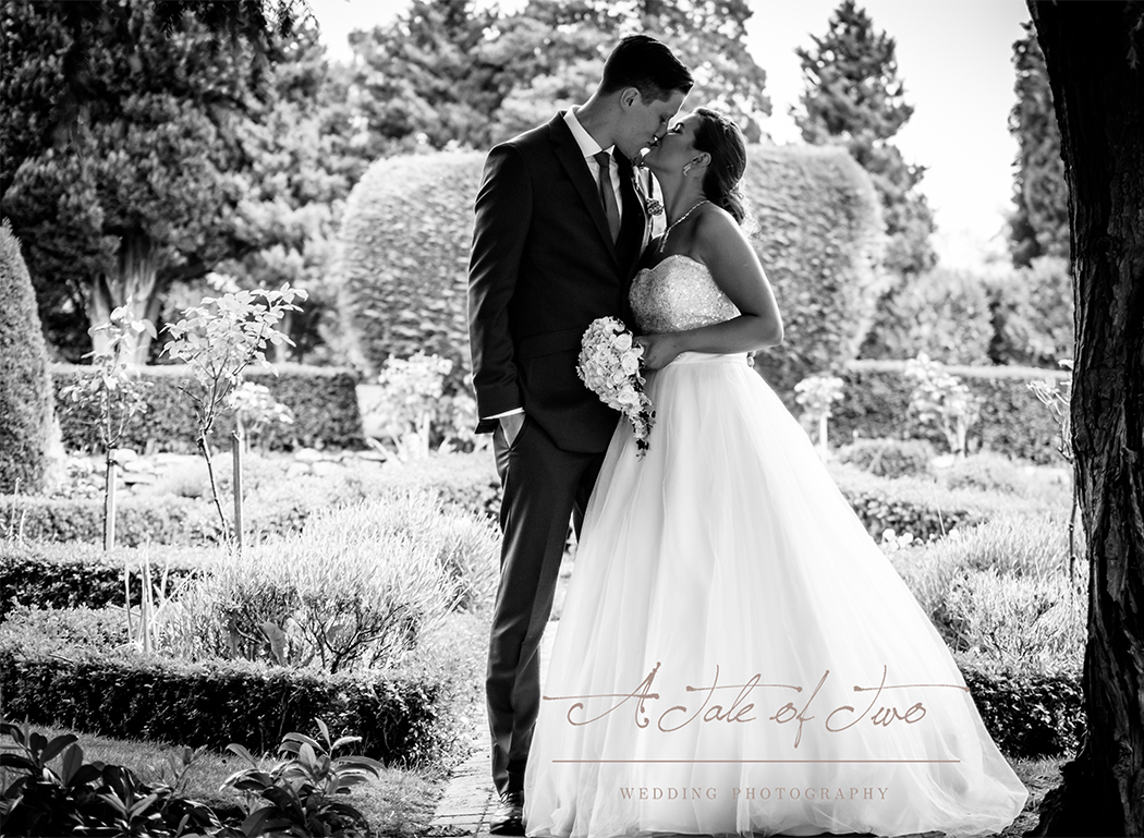 Kate and Nathan, newlyweds kissing in the gardens at Mottram Hall, Cheshire...for booking info please visit www.ataleoftwo.co.uk
